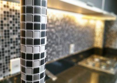 Ao fundo da imagem, há um adesivo preto na cozinha.
