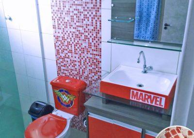 Ao fundo da imagem, há um adesivo vermelho vermelho da Super Girl no banheiro.