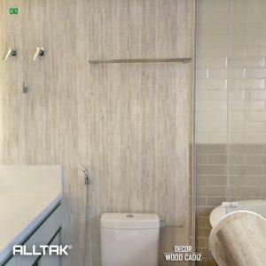 Ao fundo da imagem, há um móvel no banheiro com textura de madeira.