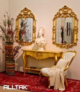 Ao fundo da imagem, há dois espelhos com molduras douradas pendurados na paredes, entre eles há uma mesa pequena encostada na parede, também dourada, com uma estátua em cima, além de uma cadeira branca com detalhes dourados na diagonal da mesa.