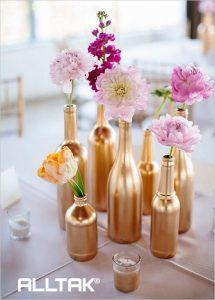 Ao fundo da imagem, há pintura dourada em garrafas e flores dentro.