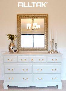 Ao fundo da imagem, há uma cômoda branca com detalhes dourados e em cima dela há um espelho, velas e um vaso com detalhes dourados.